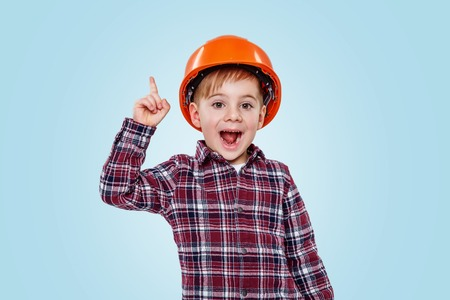 Small architect boy with helmet pointing up to copy space and smiling isolated on blue background