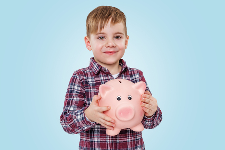 Portrait of a smiling little boy holding piggy money box and looking at camera over blue background