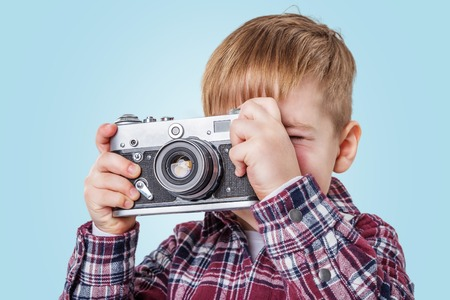 Close up portrait of a little boy taking picture with retro camera over blue background Stock Photo