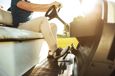 그린 코스를 따라 골프 카트를 운전하는 젊은 남자의 자른 이미지