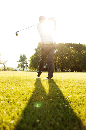 Professional male golf player hitting ball with a driver from a tee