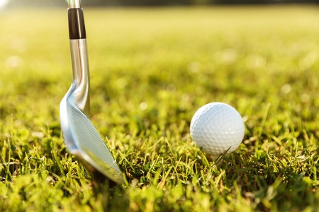 Close up of a golf club and a ball in green grass on a course 版權商用圖片