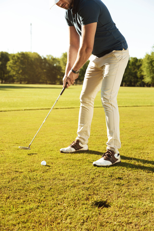 緑のコースでゴルフ ・ ボールをティーオフする男性ゴルファーのイメージをトリミング 写真素材