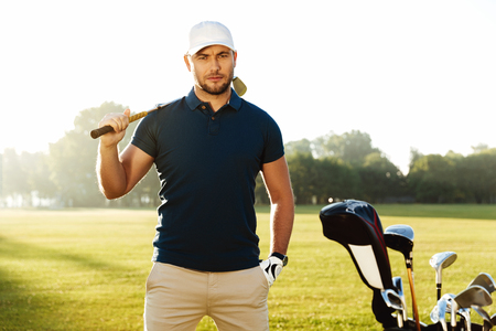 Handsome confident male golfer standing with golf club on a green field