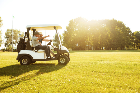 Two male golfers driving in a golf cart along green course 스톡 콘텐츠