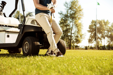 Cropped image of a male golfer leaning on a cart and holding golf club outdoors 스톡 콘텐츠
