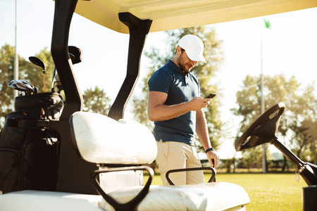 Young man using mobile phone while standing at a golf cart on a field 版權商用圖片 - 85240328