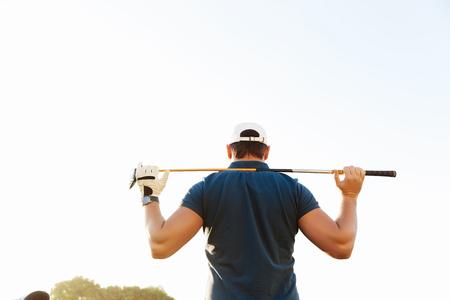 緑のコースに立っている間ドライバーを保持している男性ゴルファーの背面図 写真素材