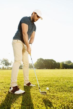 緑のコースでゴルフ ・ ボールをティーオフする男性ゴルファー