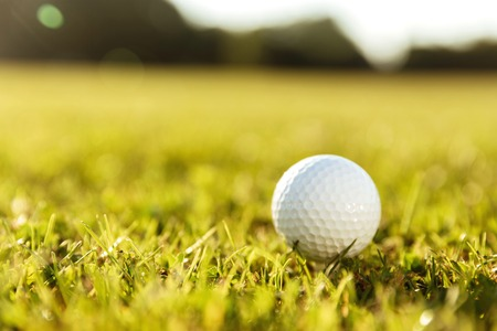 Close up of a golf ball on a tee in green grass
