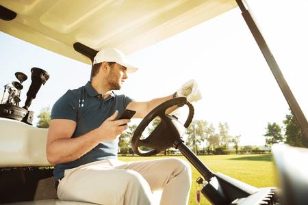 Jonge sportman drijvende golfkar terwijl het gebruiken van mobiele telefoon