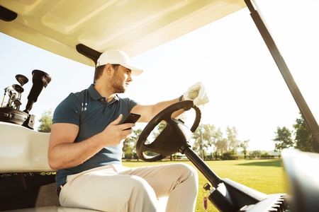 Young sportsman driving golf cart while using mobile phone Banco de Imagens