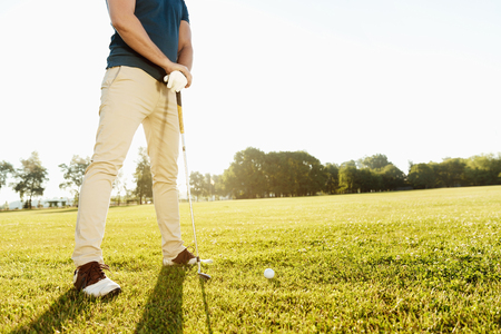 緑の屋外にゴルフボールを置く準備ゴルファーのトリミングされた画像 写真素材