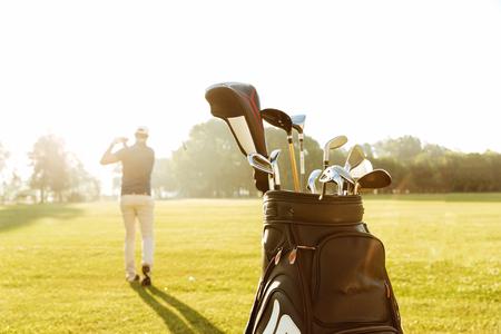 Achtermening van een mannelijke golfspeler slingerende golfclub en volgende schot in de lucht