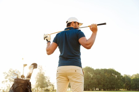 Back view of a male golf player at the green course with a club sack