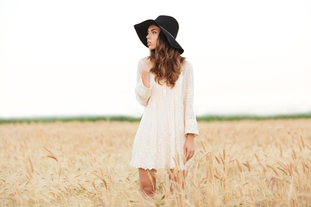 Beautiful young girl with long hair and hat posing while standing at the meadow Stock Photo