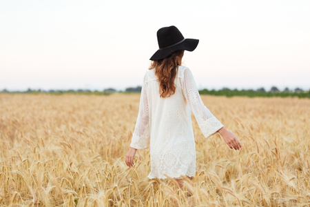 Back view of a young carefree woman with long hair in hat walking at the wheat field Stock Photo