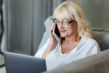 Mature woman using laptop computer while sitting on a couch and talking on mobile phone at home