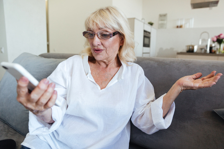 Frustrated mature woman in eyeglasses looking at mobile phone while sitting on a couch at home