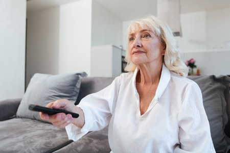 Mature woman holding tv remote control while sitting on a sofa at home