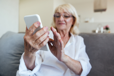 Mature woman in eyeglasses using mobile phone while sitting on a couch at home