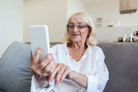 Smiling mature woman in eyeglasses using mobile phone while sitting on a couch at home