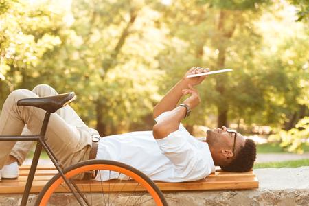 Photo de jeune homme africain tôt le matin avec vélo en plein air. Regardant de côté à l'aide de la tablette tactile. Banque d'images - 85242813