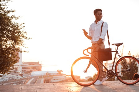 Image of young african man early morning standing near bicycle looking aside chatting by phone outdoors.