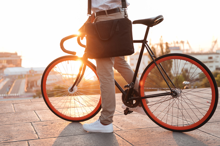 Cropped photo of young african man early morning with bicycle outdoors.