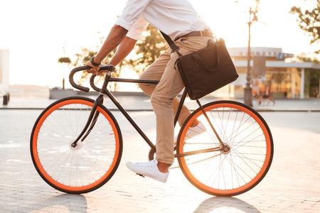 Omgekeerde foto van knappe jonge Afrikaanse man vroege ochtend met fiets lopen buitenshuis. Stockfoto