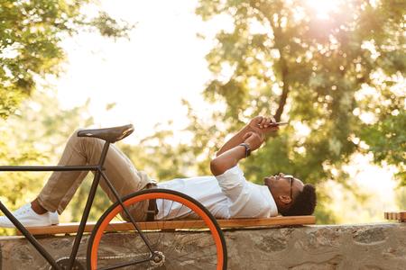 Foto van jonge Afrikaanse man vroege ochtend met fiets in openlucht. Zoek opzij met behulp van tablet pc.
