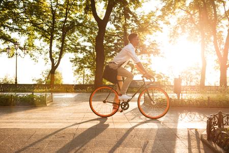 Beeld van de jonge Afrikaanse mens vroege ochtend met fiets die in openlucht loopt. Opzij kijken. Stockfoto