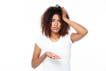 Image of sad young african lady standing isolated over white background. Looking aside holding pills with headache.