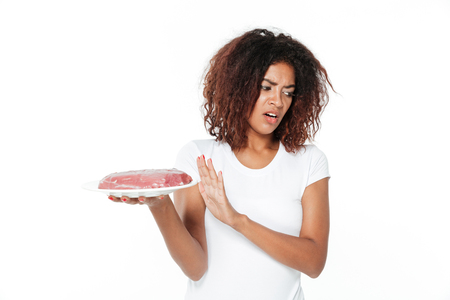Image of sad young african woman standing isolated over white background. Looking aside holding meat.