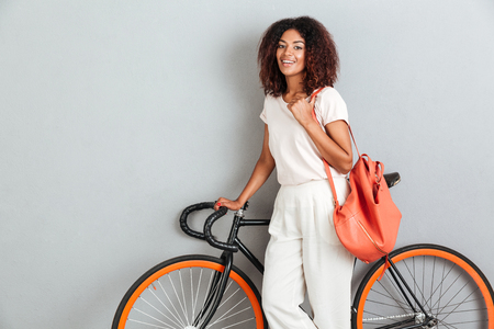 Happy african woman posing with bicycle and backpack over gray background Imagens - 85428390