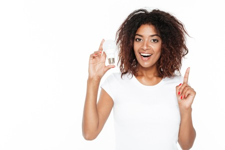 Picture of cheerful young african woman standing isolated over white background. Looking camera holding lamp have an idea. Banco de Imagens - 85361989