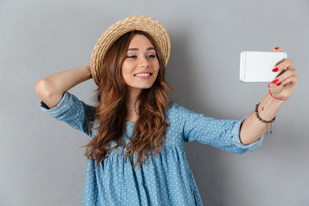 Image of happy young caucasian lady make selfie by phone. Looking aside.