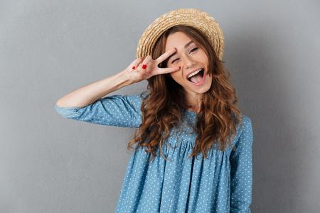 平和のジェスチャーを示す帽子をかぶった灰色の壁の上に立っている笑顔の若いかわいい女性の写真。カメラを探しています。