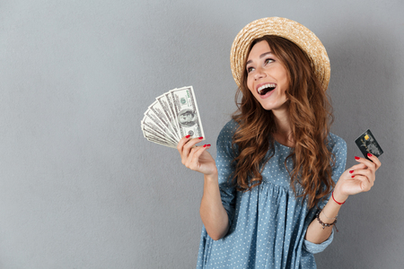帽子を持って金とクレジットカードを身に着けている灰色の壁の上に立って幸せな若いかわいい女性の写真。 写真素材