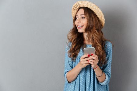 Afbeelding van gelukkige jonge Kaukasische dame op de telefoon praten. Opzij kijken. Stockfoto