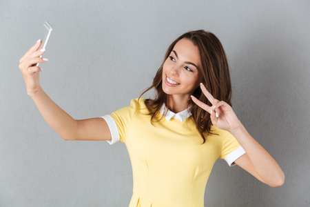 Smiling pretty girl showing peace gesture while taking a selfie isolated over gray background