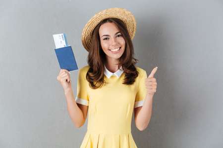 Pretty happy girl in hat holding passport with tickets and showing thumbs up gesture isolated over gray background