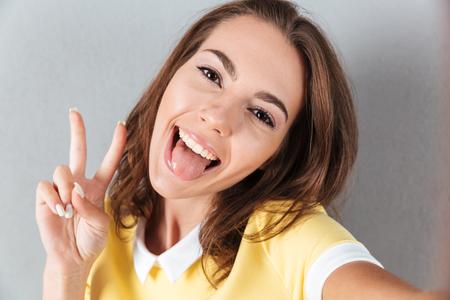 Glimlachend mooi meisje die een selfie met haar tong nemen die uit over grijze achtergrond wordt geïsoleerd