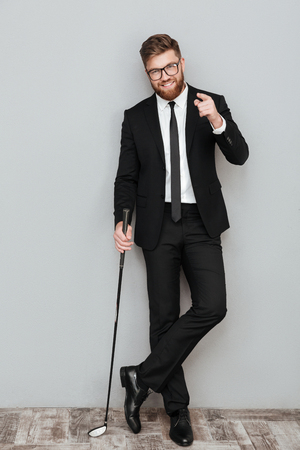 Full length portrait of a smiling bearded businessman in suit standing and holding golf club isolated over gray background