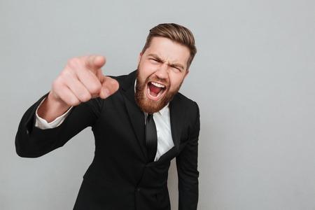 hombre de negocios enojado enojado en traje gritando y apuntando dedo en cámara aislada sobre fondo gris