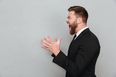 Side view of a angry bearded man in suit shouting and gesturing with hands isolated over gray background