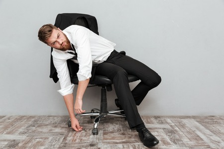 Tired drunk businessman resting in office chair isolated over gray background Stock Photo - 85453873