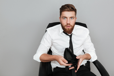 Shocked bearded man in white shirt showing empty wallet while sitting in chair isolated over gray background
