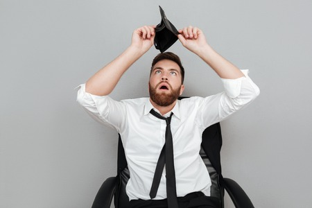 Frustrated surprised bearded man in white shirt showing empty wallet while sitting in chair isolated over gray background