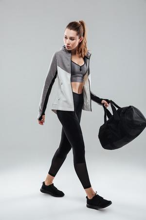 Volledig lengteportret van een jonge fitness vrouw die met sportenzak loopt die over grijze achtergrond wordt geïsoleerd